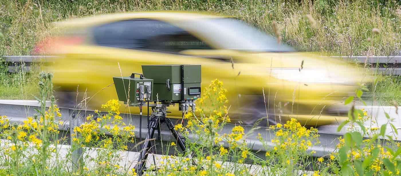 Ein rasendes gelbes Auto wird geblitzt
