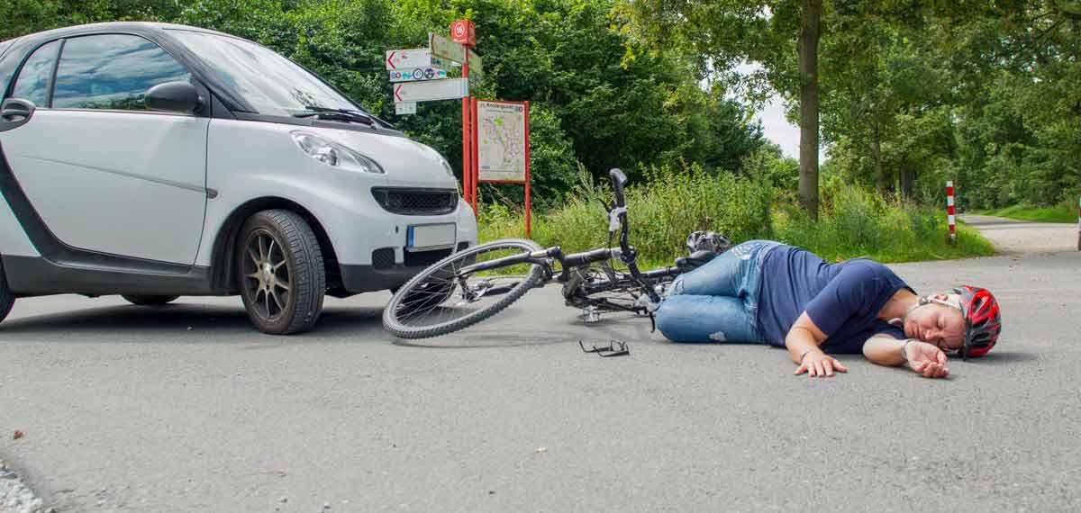 Frau ist mit Ihrem Fahrrad von einem KFZ angefahren worden und liegt reglos auf der Straße.